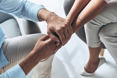 Feeling loved. Close up top view of young couple holding hands while sitting indoors Stock Photo
