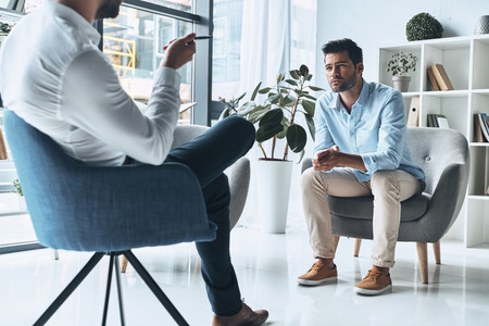 Sharing his problems. Young frustrated man solving his mental problems while having therapy session with psychologist Banque d'images - 106880733
