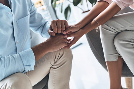 Loving couple. Close up of young couple holding hands while sitting indoors