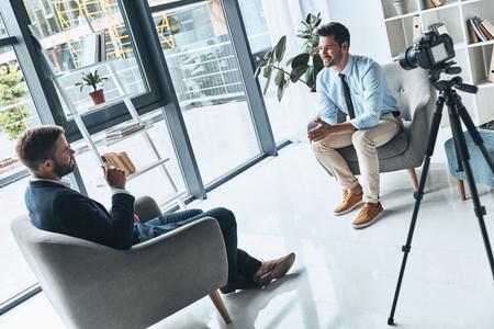 Geschäftsinterview. Zwei junge Männer in schicker Freizeitkleidung unterhalten sich, während sie drinnen ein neues Video machen