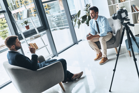 Zakelijk interview. Twee jonge mannen in slimme vrijetijdskleding praten terwijl ze binnenshuis een nieuwe video maken
