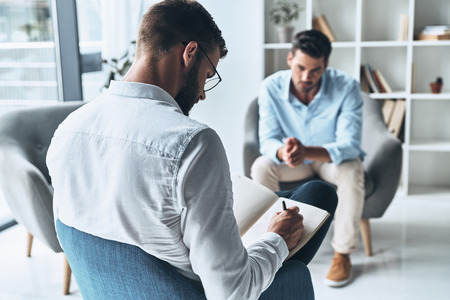 Facing social difficulties. Young frustrated man solving his mental problems while having therapy session with psychologist Banque d'images - 106880786