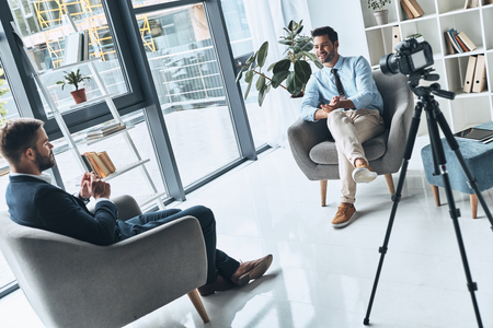 Business vlog. Two young men in smart casual wear talking while making new video indoors Stock Photo