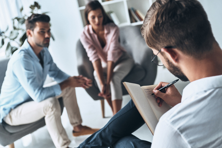 Making notes. Young married couple talking while sitting on the therapy session with psychologist Banque d'images - 106880811