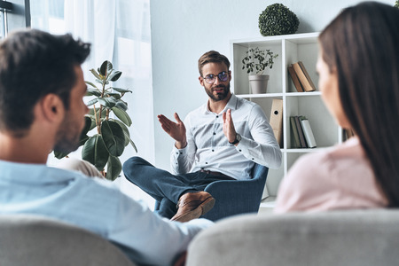 Helping couples. Young married couple listening to psychologist while sitting on the therapy session Foto de archivo - 106880819