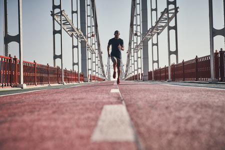 Always in great shape. Full length of young African man in sports clothing exercising while jogging on the bridge outdoors