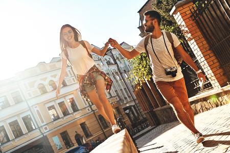 Enjoying every minute together. Full length of young couple holding hands and smiling while walking outdoors Stock Photo