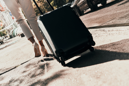 Business travel. Close up rear view of young woman pulling luggage while walking outdoors