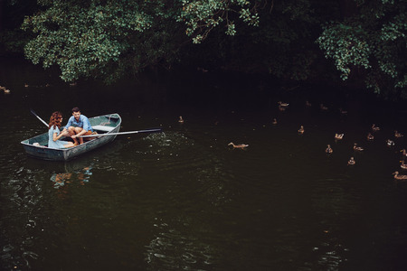Beauty of nature. Top view of beautiful young couple feeding ducks while rowing a boat