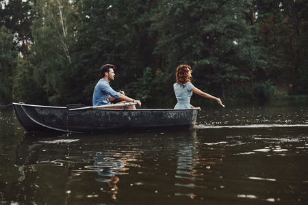 Young and free. Beautiful young couple enjoying romantic date while rowing a boat Banco de Imagens