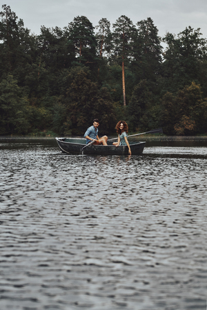 Moments of joy. Beautiful young couple enjoying romantic date and smiling while rowing a boat