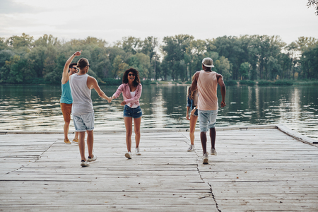 Full length of young people in casual wear smiling and dancing while standing on the pier Stock Photo
