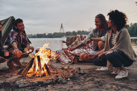 Group of young people in casual wear roasting marshmallows over a campfire while resting near the lake Фото со стока
