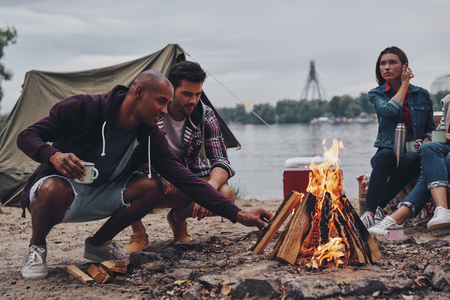 Feeling the warmness. Group of young people in casual wear smiling while enjoying beach party near the campfire Stock Photo