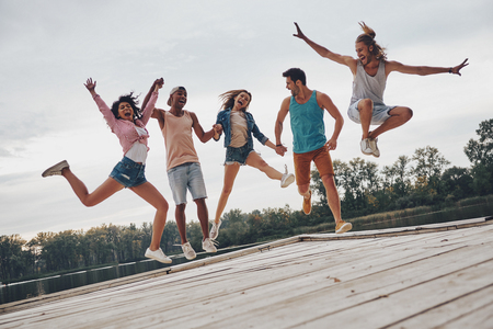 Young and full of energy. Full length of young people in casual wear smiling and gesturing while jumping on the pier
