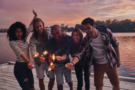 Friends make each other happy. Group of young people in casual wear smiling and holding sparkers while standing on the pier