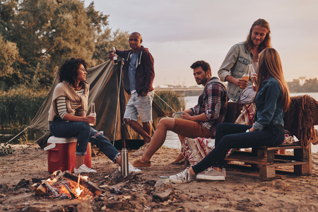 Happy to travel together. Group of young people in casual wear smiling and drinking beer while camping near the lake Stock Photo