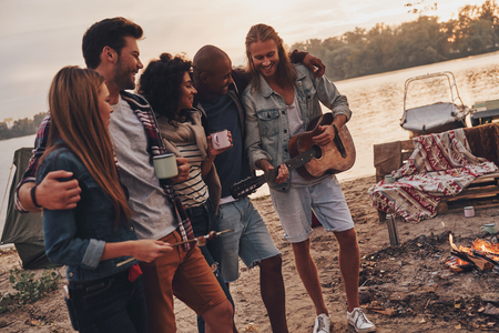 Best place to rest. Group of young people in casual wear smiling while enjoying beach party near the lake