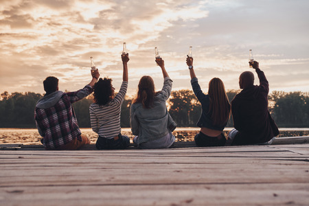 To us! Rear view of young people in casual wear toasting with a beer bottles while sitting on the pier Stock Photo