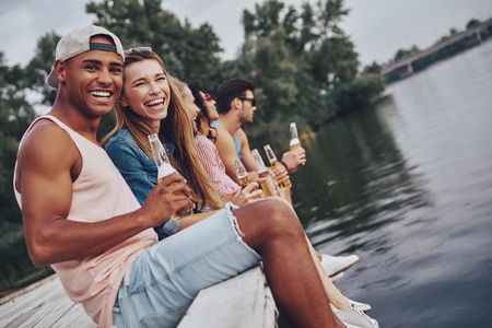 Good friends. Group of happy young people in casual wear smiling and drinking bear while sitting on the pier Stock Photo