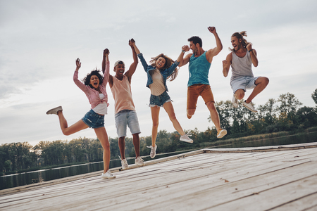 Life is better with friends. Full length of young people in casual wear smiling and gesturing while jumping on the pier