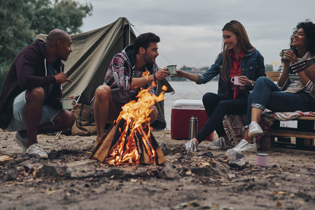 Friends make each other happy. Group of young people in casual wear smiling while enjoying beach party near the campfire Stock Photo
