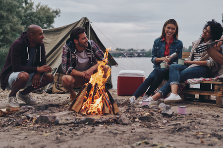 They will remember this day. Group of young people in casual wear smiling while enjoying beach party near the campfire Stock Photo