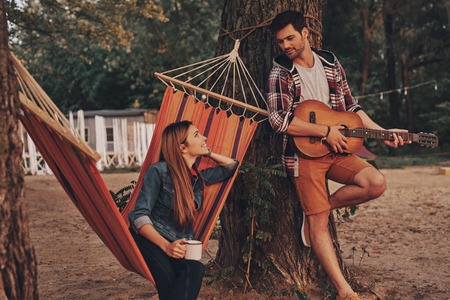Listening to the song of love. Handsome young man playing guitar for his beautiful girlfriend while spending carefree time outdoors Stock Photo