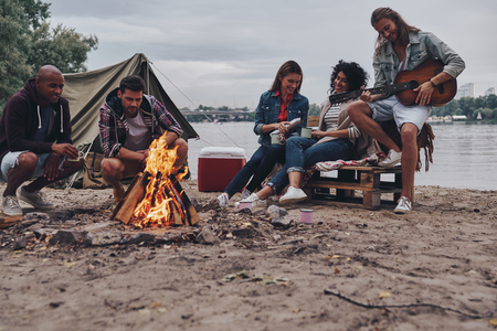 Playing favorite song. Group of young people in casual wear smiling while enjoying beach party near the campfire Stock Photo