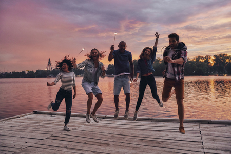 Feels like flying. Full length of young people in casual wear smiling and holding sparkers while jumping on the pier Stock Photo