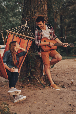 Singing for his only love. Handsome young man playing guitar for his beautiful girlfriend while spending carefree time outdoors Stock Photo
