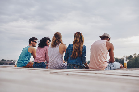 Young and carefree. Rear view of young people in casual wear smiling and talking while sitting on the pier Stock Photo