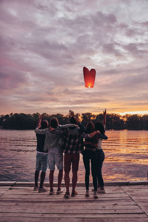 Flying away. Full length rear view of young people embracing and gesturing while looking at floating sky lantern