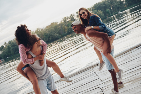 Pure happiness. Beautiful young couples spending carefree time while standing on the pier Stock Photo