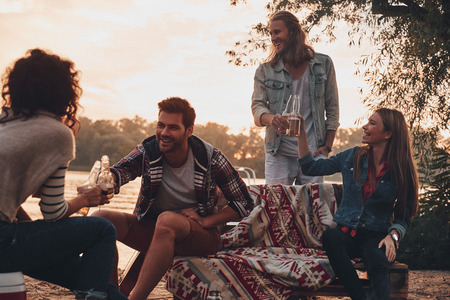Moment of real joy. Group of young people in casual wear smiling and toasting each other while enjoying beach party near the lake Stock Photo