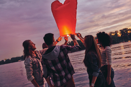 Life filled with friendship. Group of young people in casual wear preparing sky lantern while standing on the pier