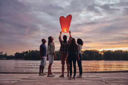 Flying away... Full length of young people in casual wear letting go sky lantern while standing on the pier Imagens