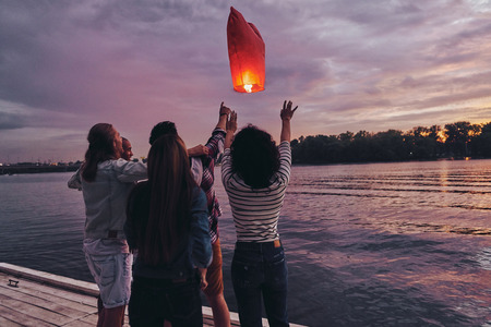 Friends forever. Group of young people in casual wear letting go the sky lantern while standing on the pier