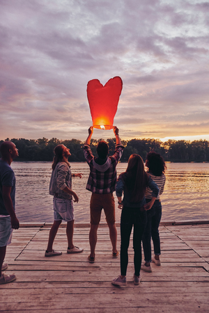 Carefree and happy. Full length of young people in casual wear preparing sky lantern while standing on the pier