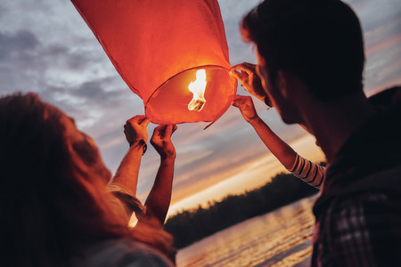 Making happy memories. Happy young people in casual wear holding the sky lantern while standing near the river