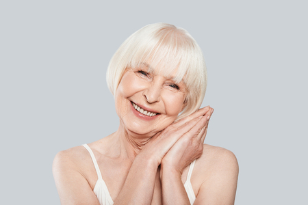 Aging process. Beautiful senior woman looking at camera and smiling while standing against grey background