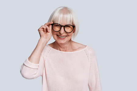 Happiness has no age. Beautiful senior woman adjusting eyewear and smiling while standing against grey background