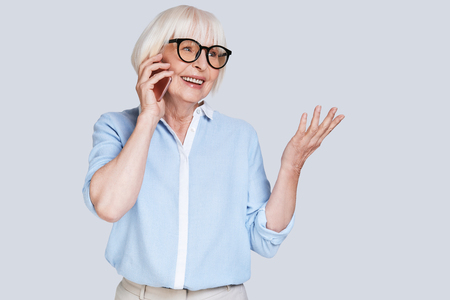 Listening to clients requirements. Beautiful senior woman talking on smart phone and smiling while standing against grey background Stock Photo