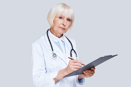 Giving a prescription. Beautiful senior woman in lab coat looking at camera and writing something down while standing against grey background