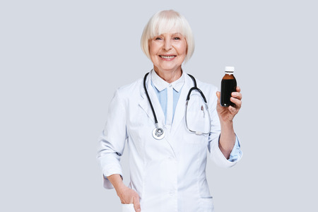 Confident pharmacist. Beautiful senior woman in lab coat holding a bottle with medicines and smiling while standing against grey background