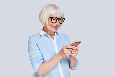 Typing business message. Beautiful senior woman using her smart phone and smiling while standing against grey background