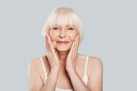 Taking good care of her skin. Beautiful senior woman looking at camera and smiling while standing against grey background Stock Photo - 109476927