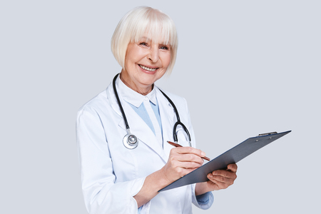 New prescription. Beautiful senior woman in lab coat looking at camera and writing something down while standing against grey background
