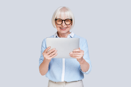 Examining her new digital tablet. Beautiful senior woman working using digital tablet and smiling while standing against grey background