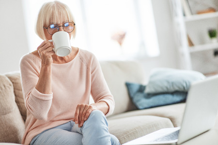 Enjoying fresh coffee at home. Beautiful senior woman drinking coffee while relaxing on the couch at home
